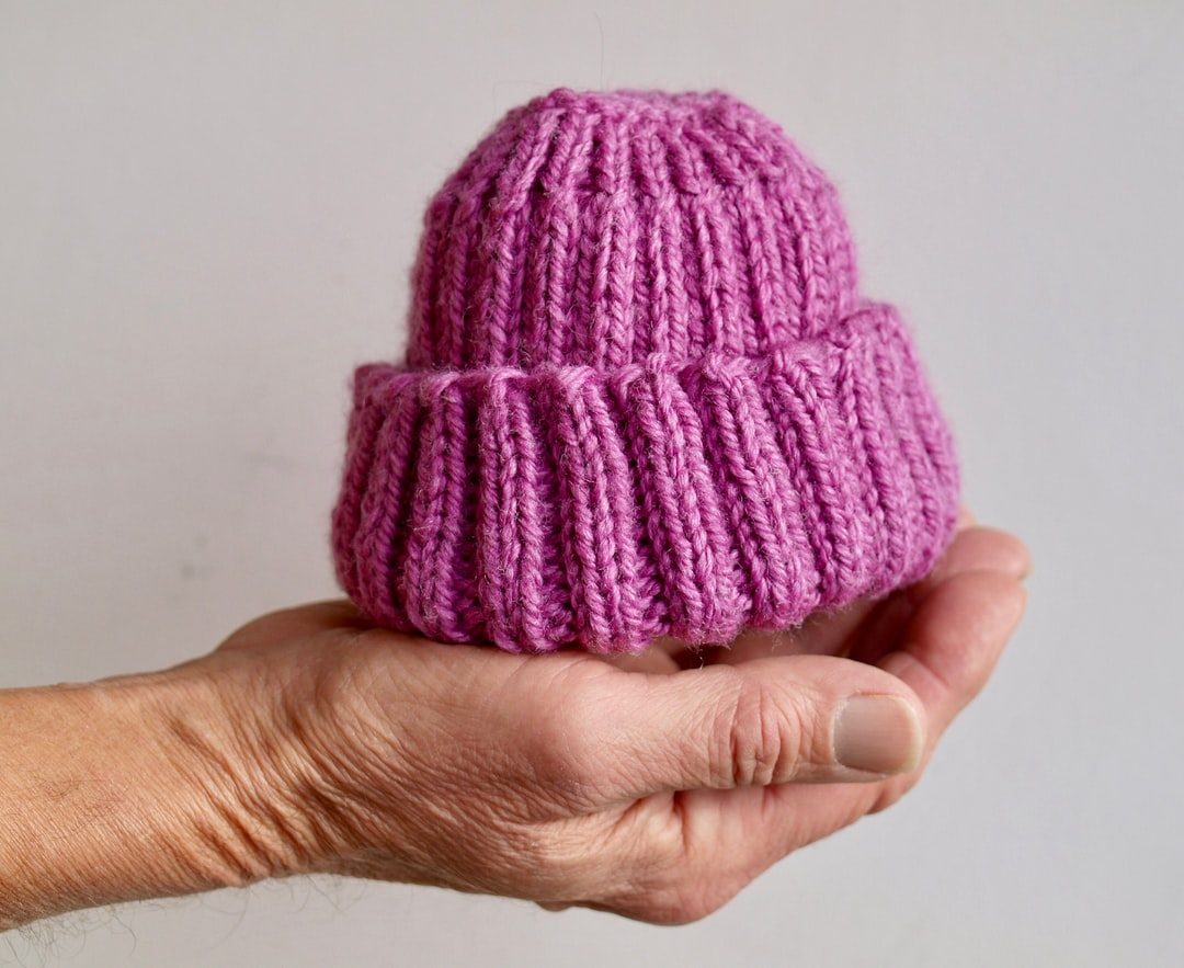 A man's hand cradles a soft knit wool watch cap baby hat in raspberry pink against a light grey background.