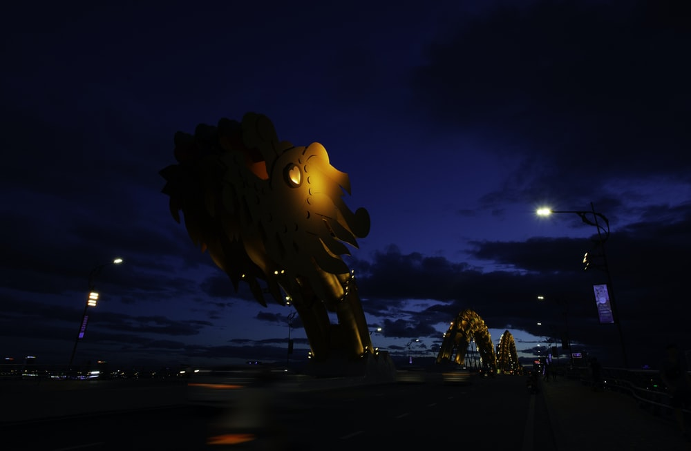 brown dragon sculpture outdoors near building during night