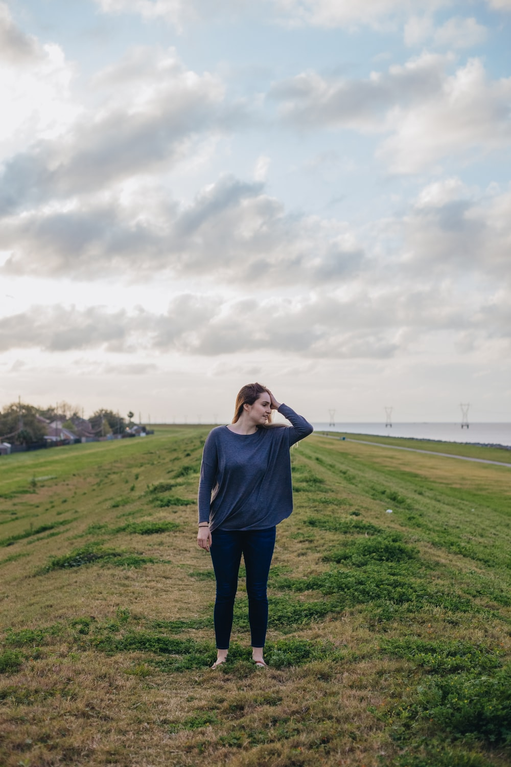 woman standing on green grass field at daytime
