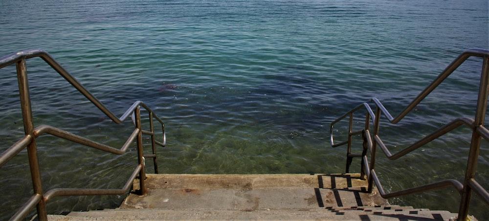 gray metal railings towards into the sea