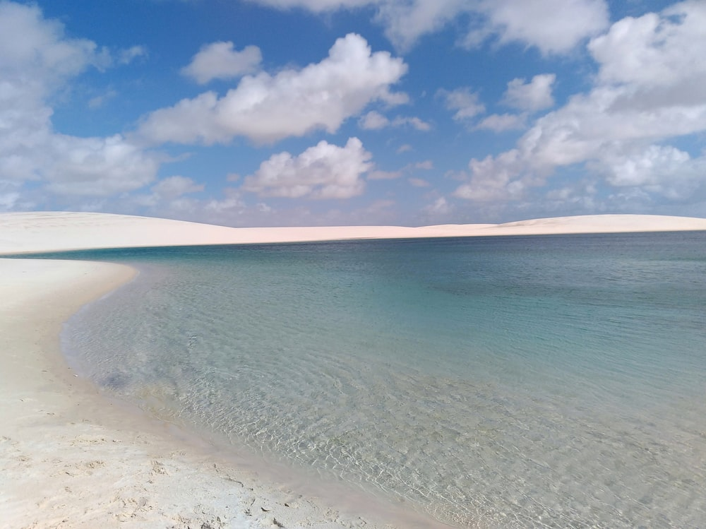 white sand beach under cloudy sky during daytime