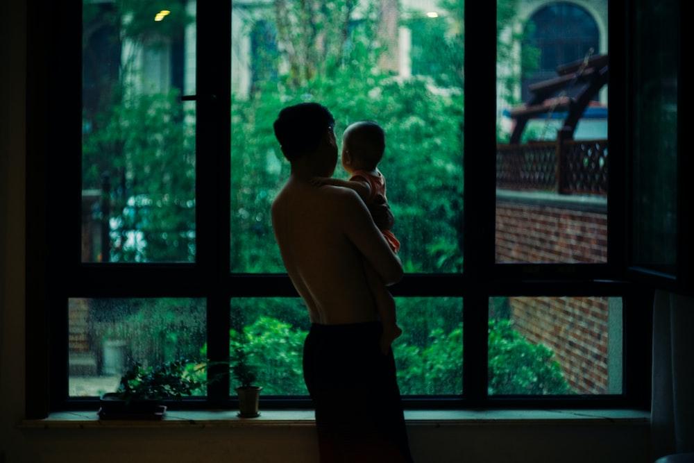 topless man carrying baby standing beside window