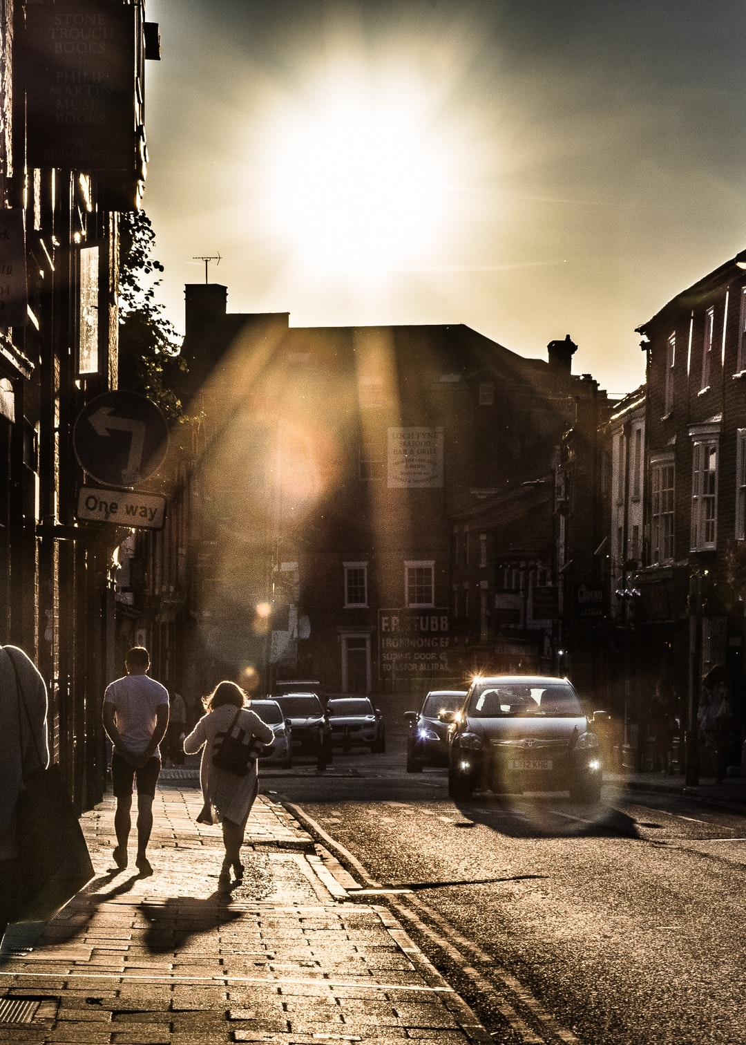 A lovely couple is walking along the street in the evening with the sun light.