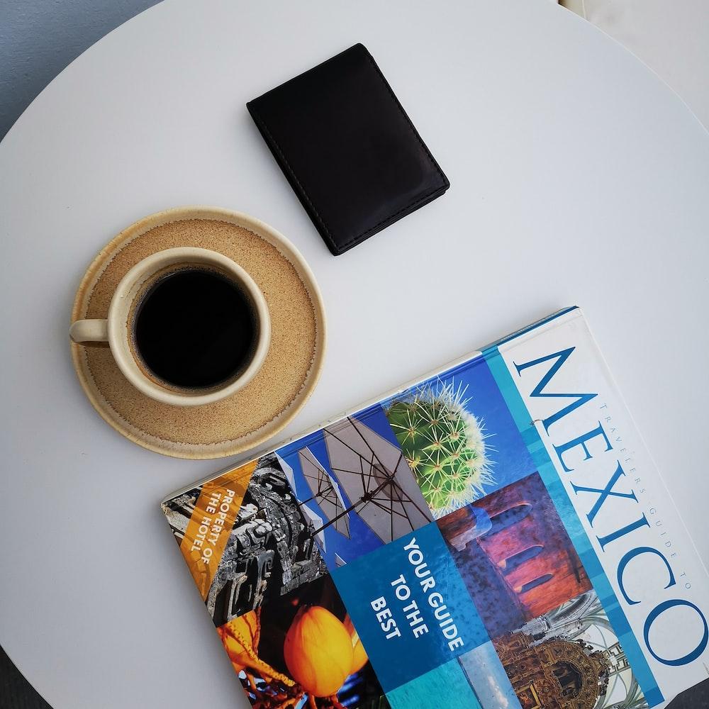 black wallet beside coffee filled mug on saucer