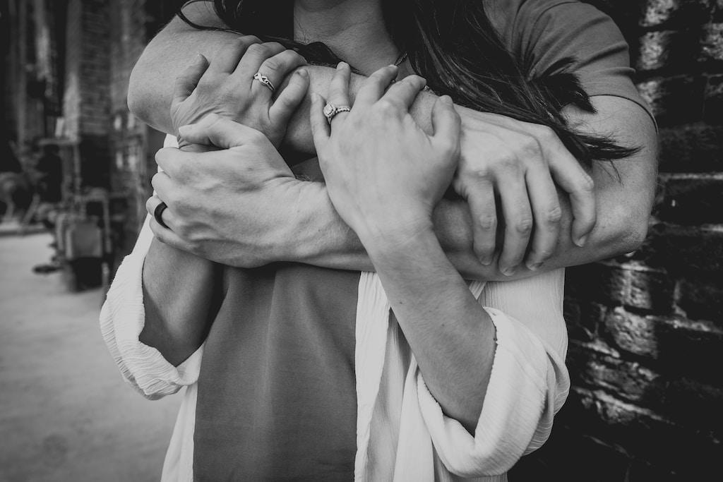 grayscale photo of man hugging woman