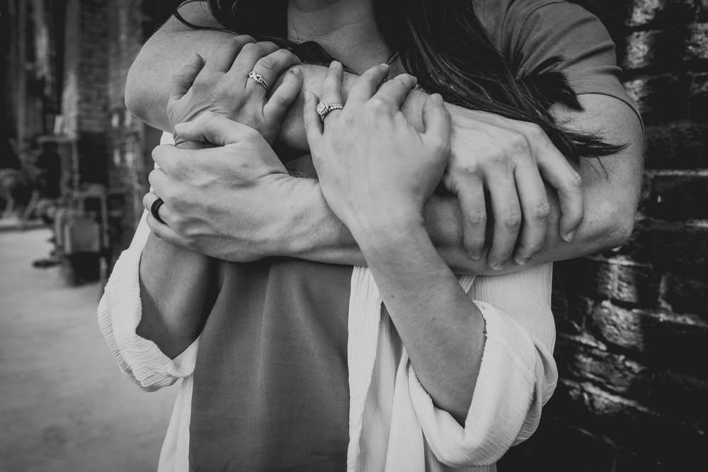 grayscale photo of man hugging woman