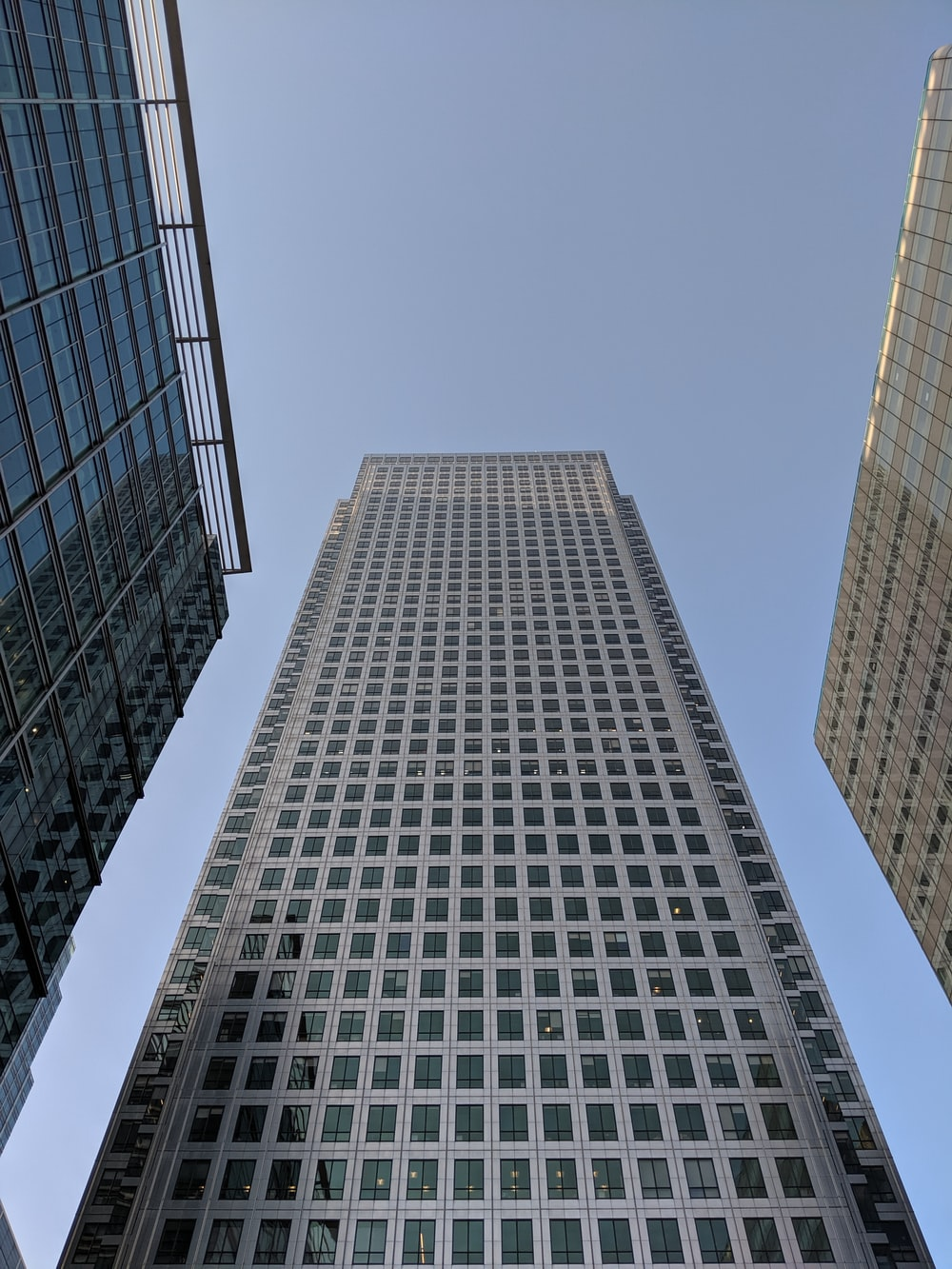 low-angle photography of white glass building under calm blue sky