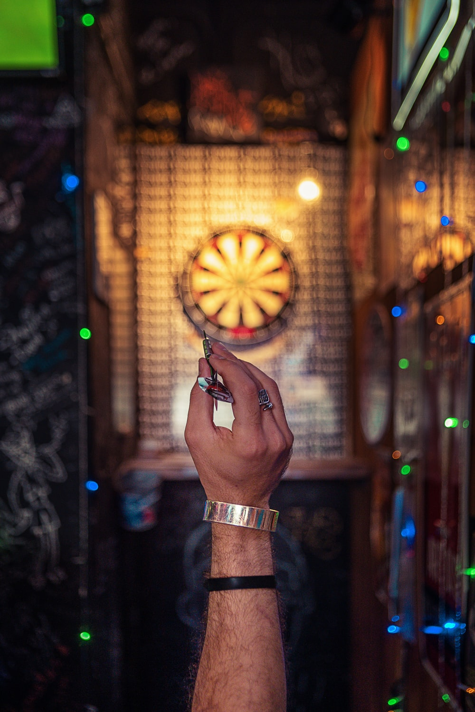 person aiming on dartboard