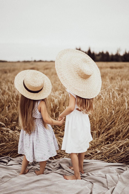 two girls wearing straw hat