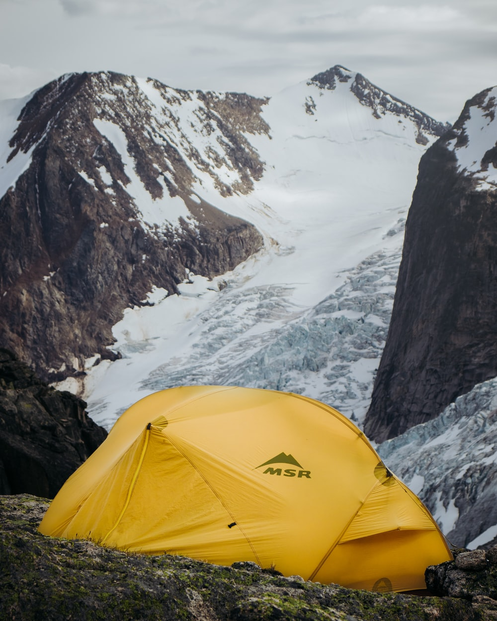 yellow camping tent near mountains during daytime