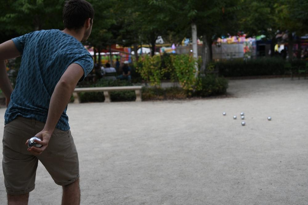 man throwing gray steel ball