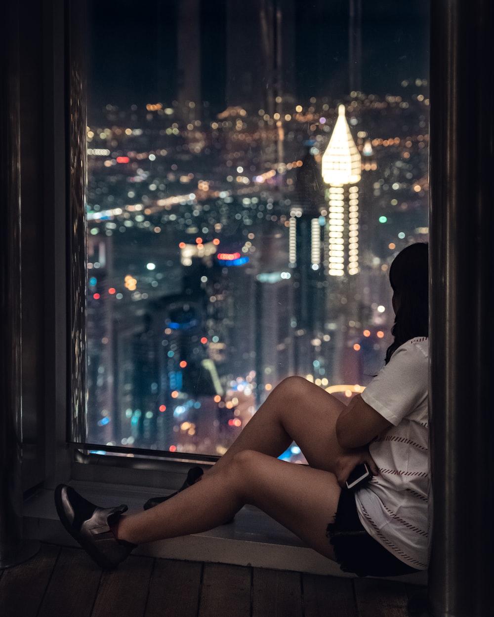 woman sitting beside window during nighttime
