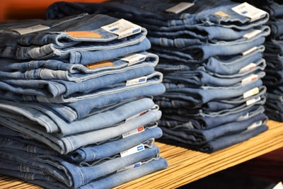 pile of blue denim jeans lot style teams background