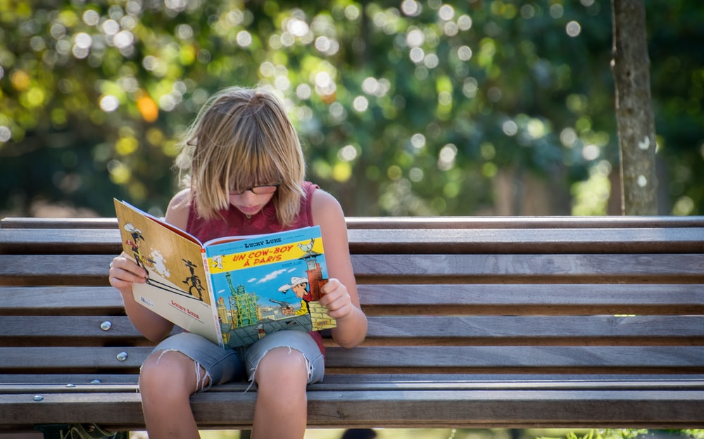 girl in red top sitting on bench while reading