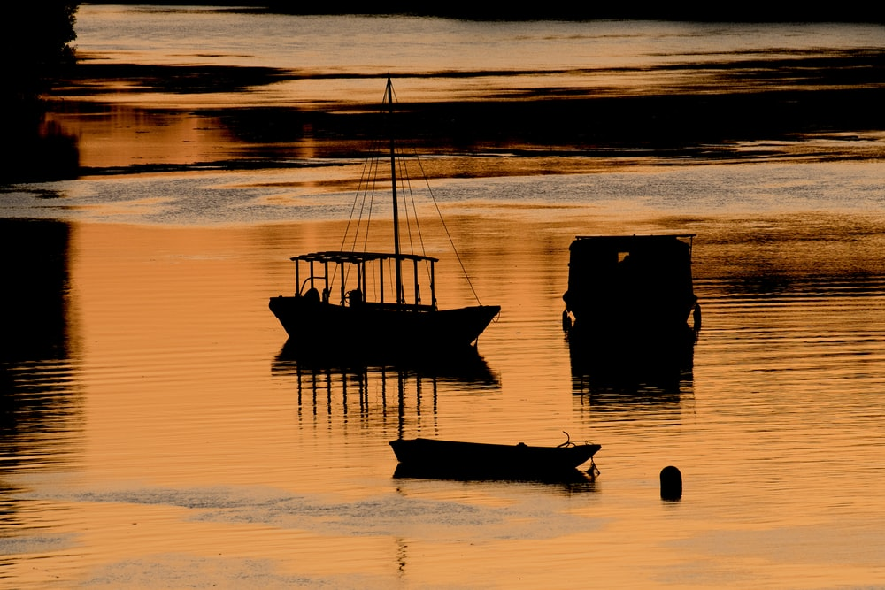 two boats on calm body of water during golden hour