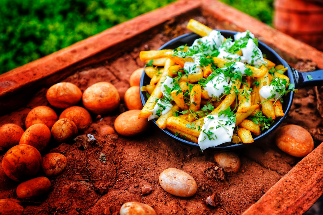 A pan containing Jalapeno French Fries are kept on stones.