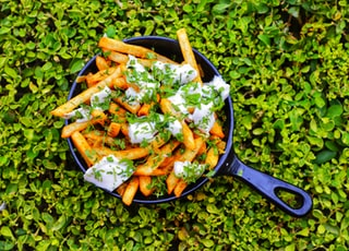 Jalapeno French Fries are kept in a pan which is kept on green bushes.