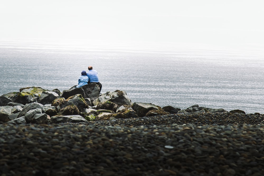 man and woman in blue shirts sitting on rock at the beach