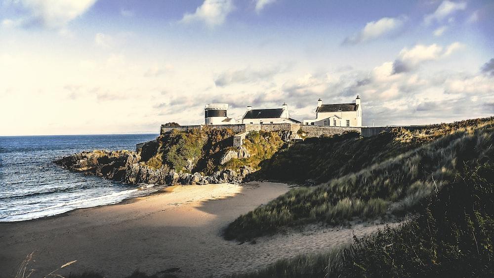 three white concrete houses on sea cliff during daytime