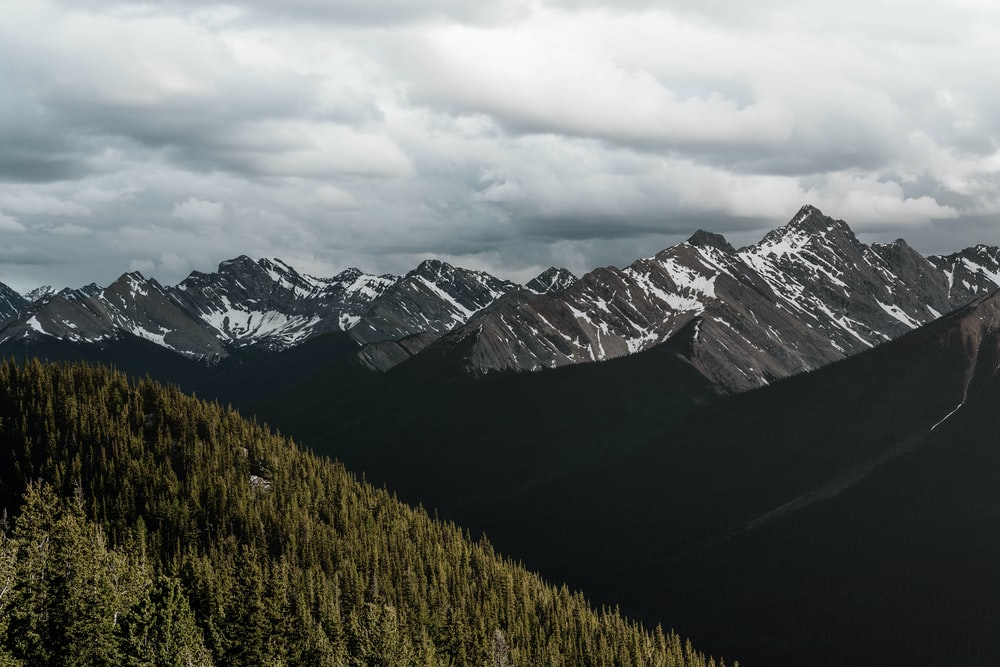 snow-capped gray rocky mountain under cloudy sky during daytime