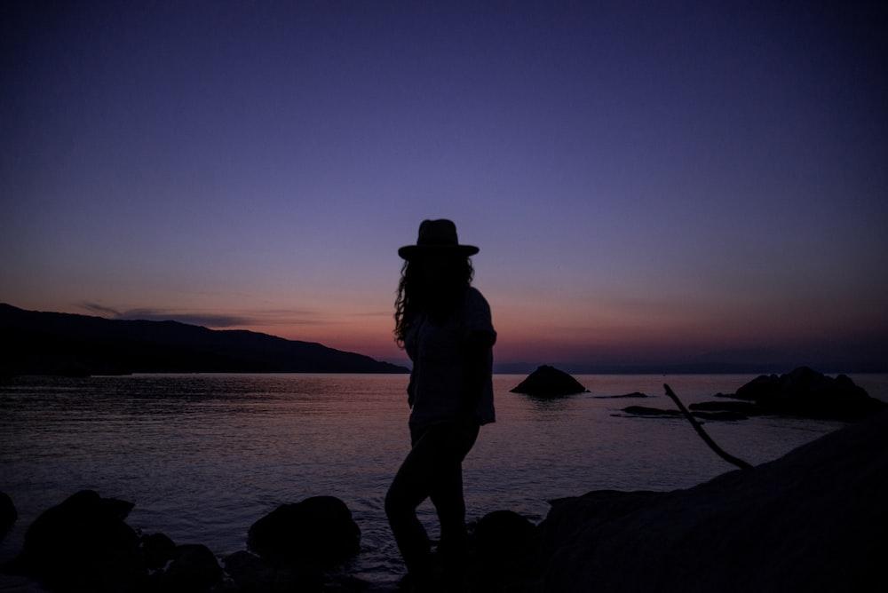 silhouette of person near ocean