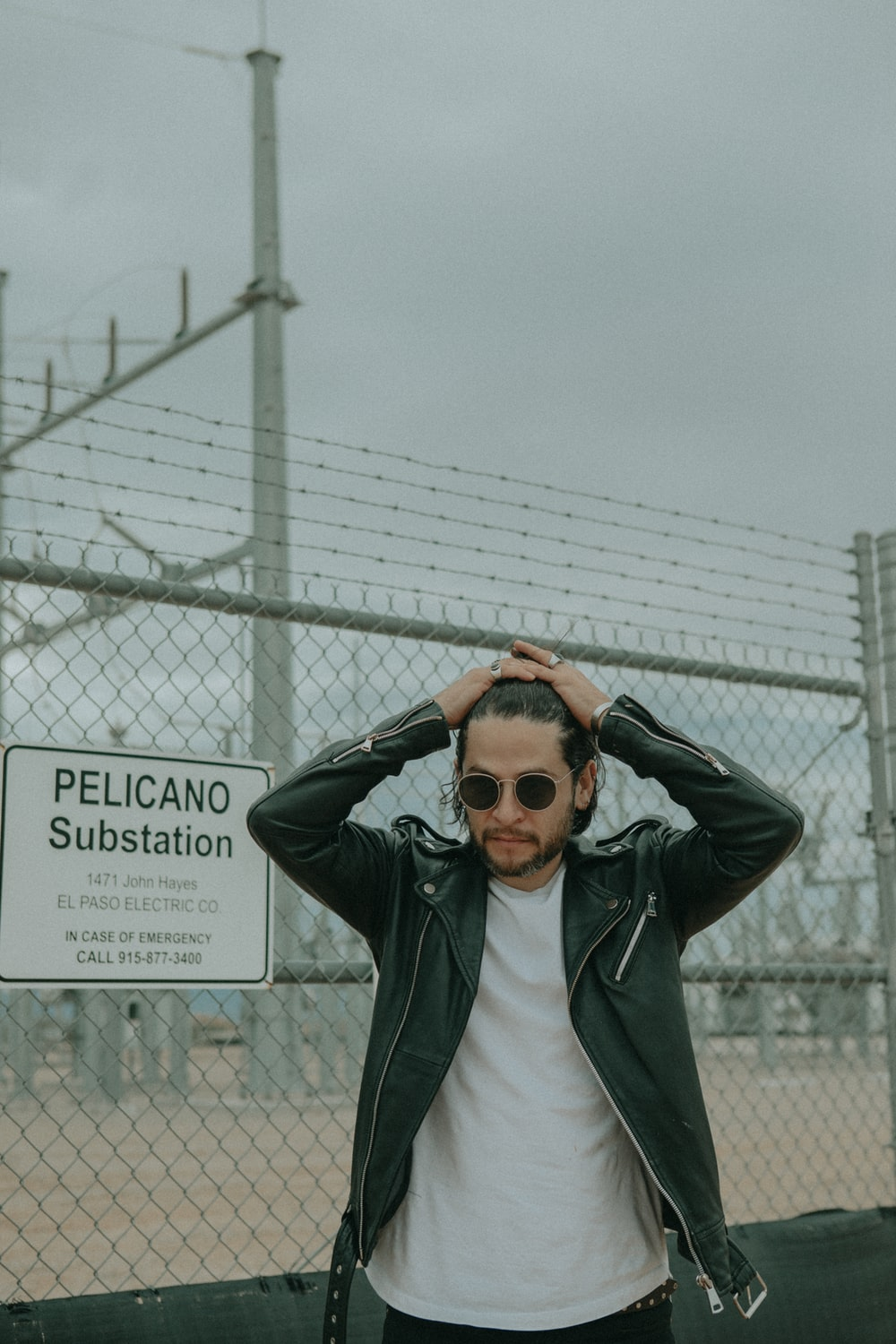 man wearing black leather jacket standing beside chain link fence