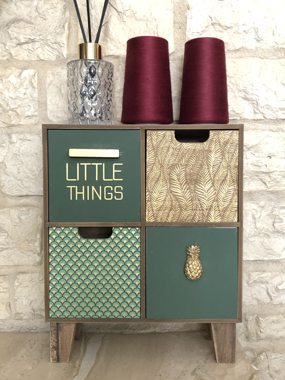 two maroon sewing threads on cube shelf