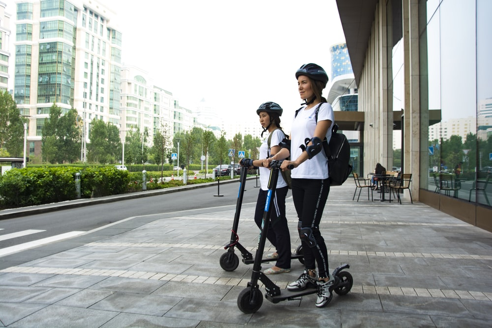 two women riding kick scooters
