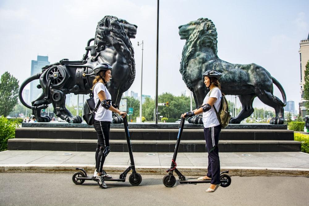 woman standing beside kick scooter