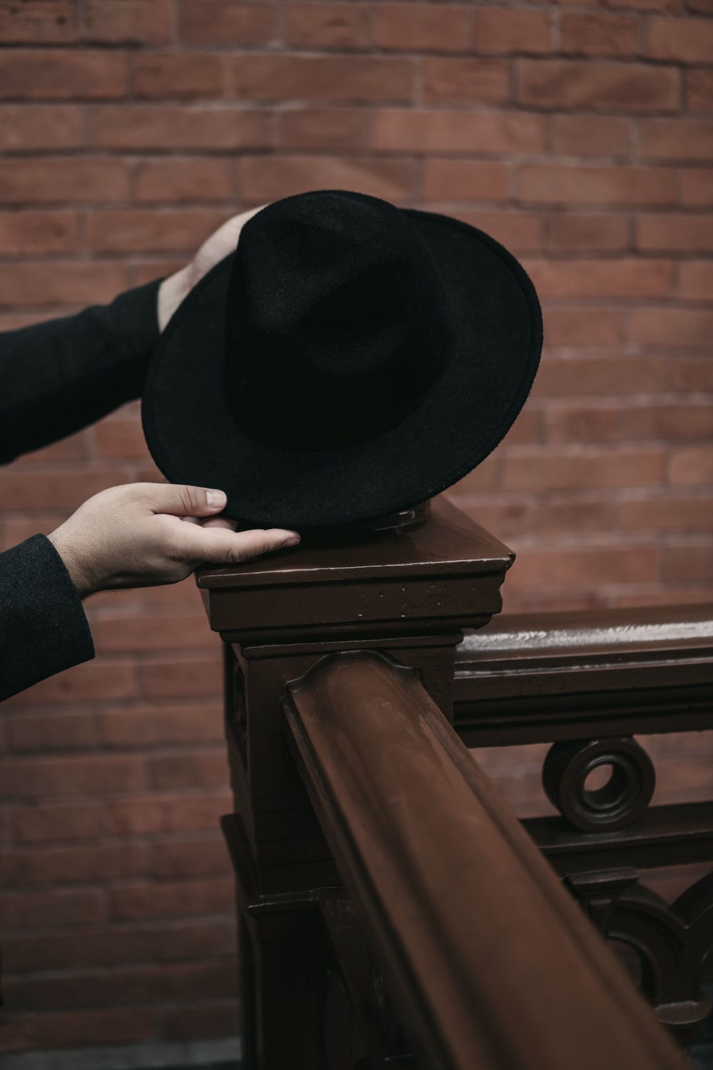 person holding black hat