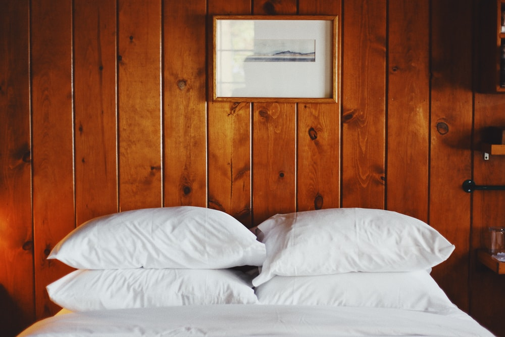 four white pillows in front of brown wooden wall