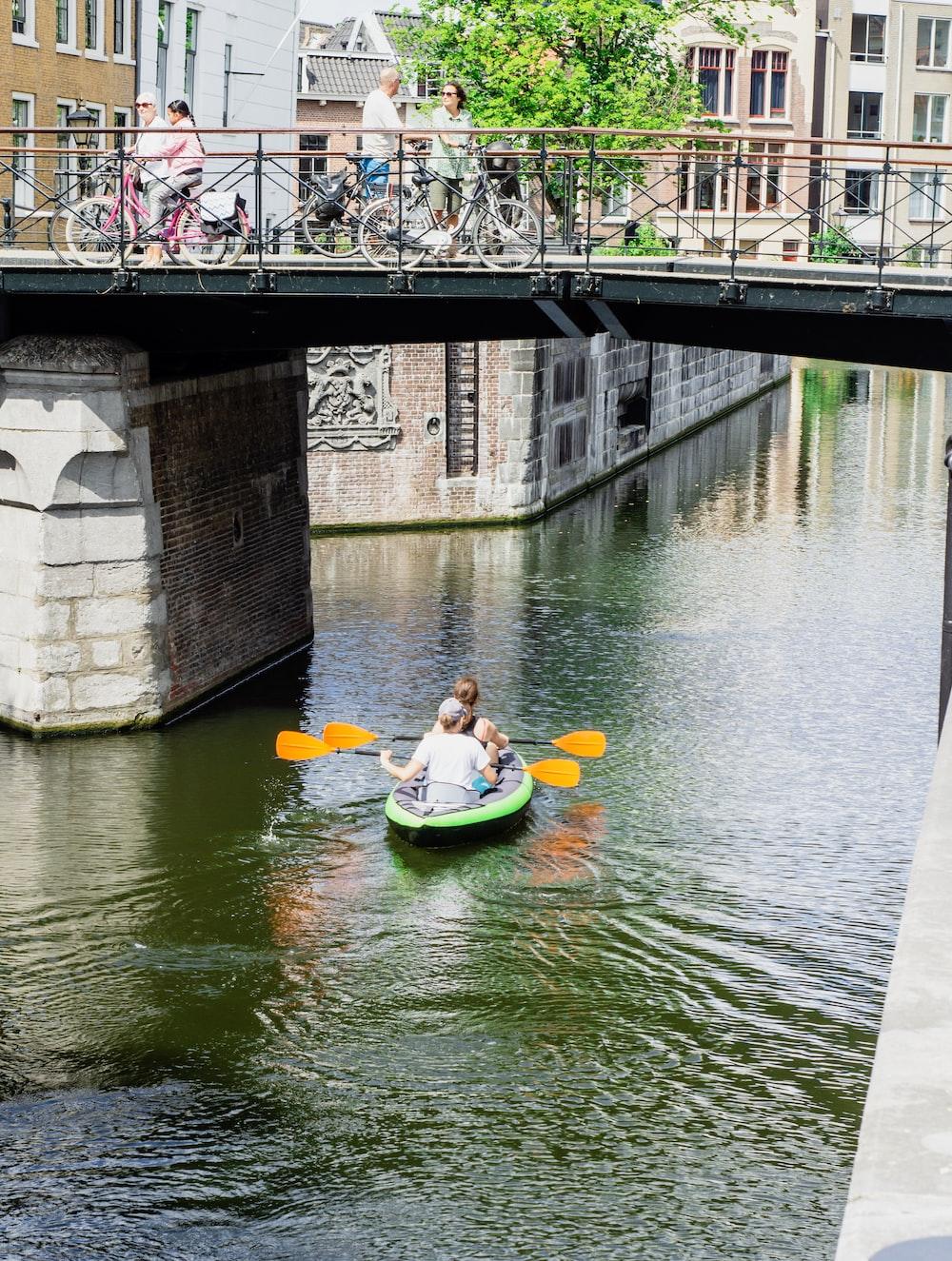 two people kayaking under bridge