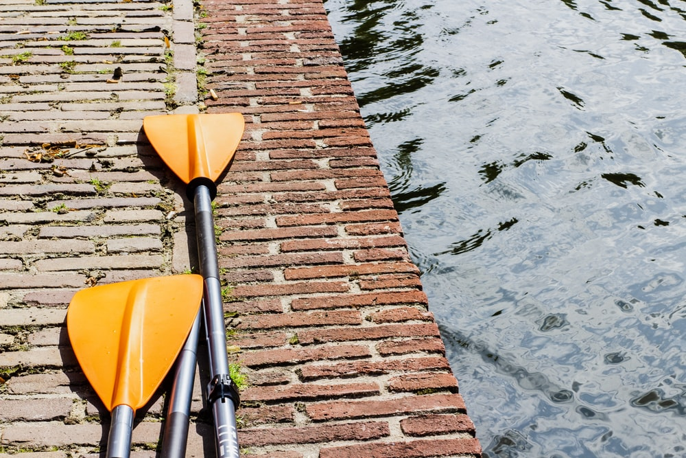 pair of yellow and silver paddles on gray surface