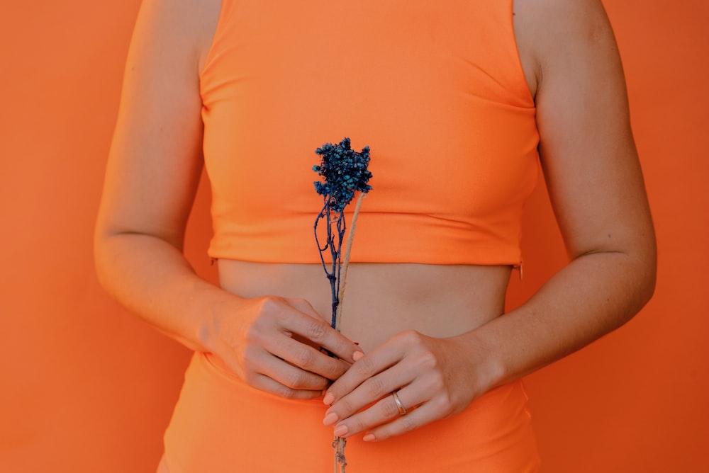 woman holding blue petaled flower