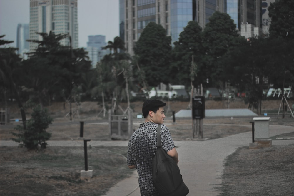 man in gray shirt standing on pathway