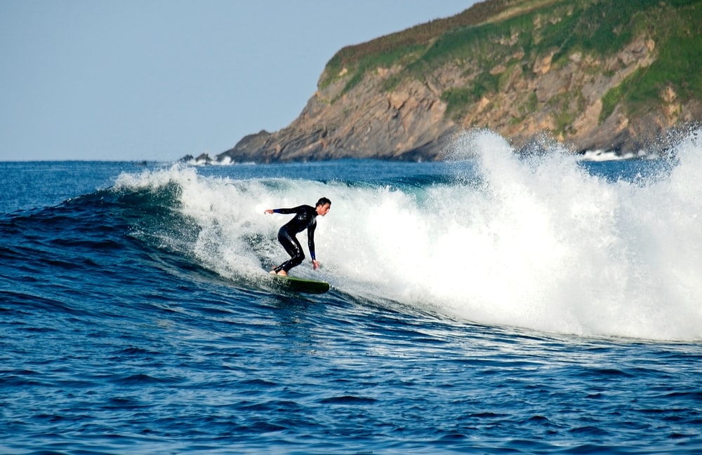 person wearing black wetsuit riding surfboard on body of water