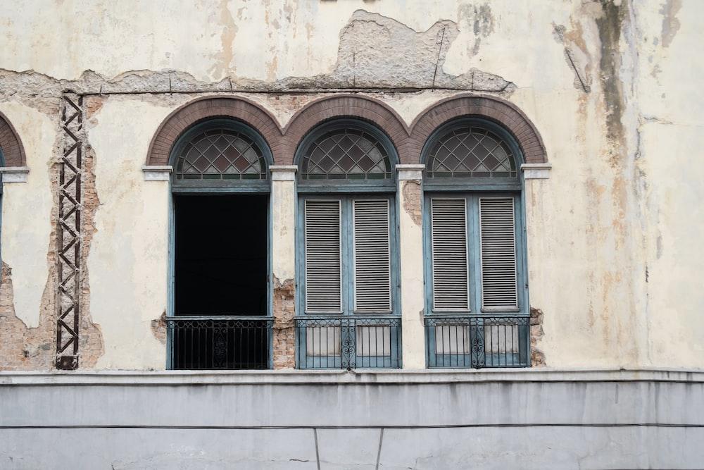 three blue wooden windows on concrete wall