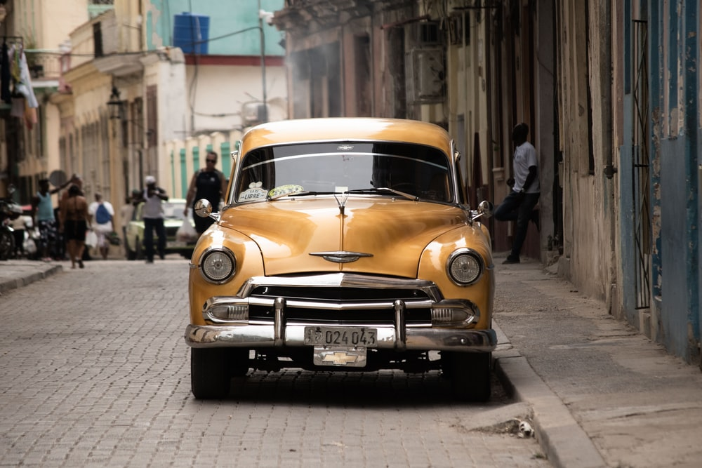 classic yellow car on alleyway