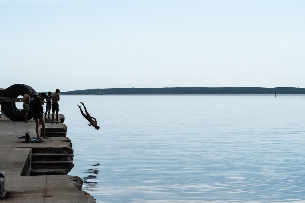 man diving head first from dock