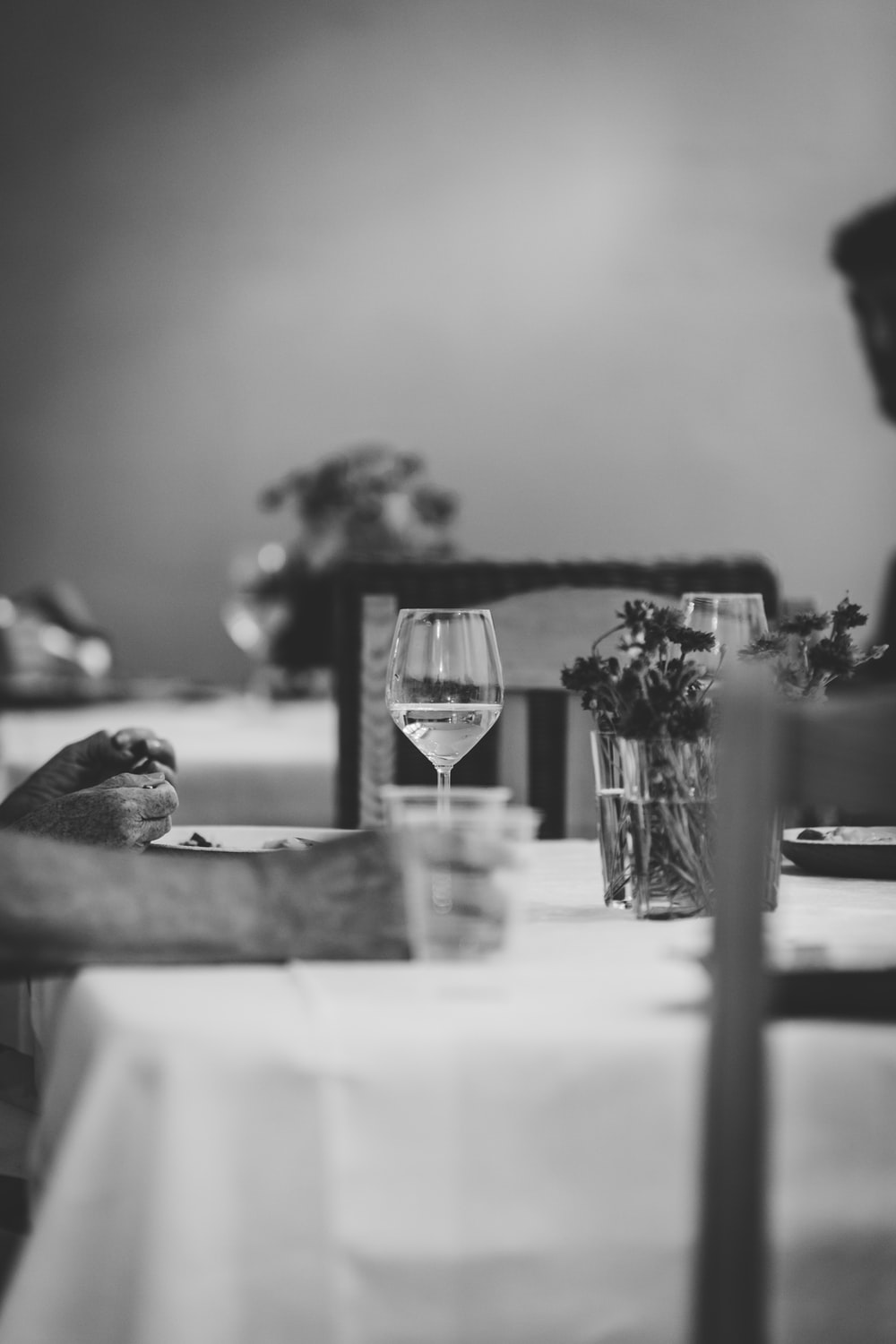 grayscale photography wine glass on top of table