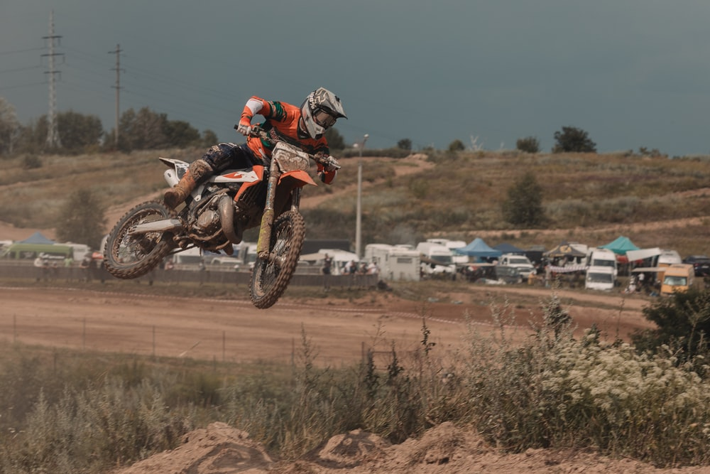 man riding dirt bike in mid air during day