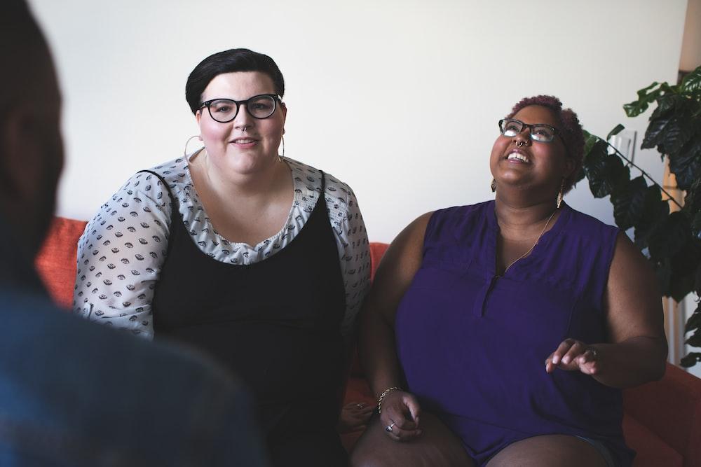 two women sitting on sofa