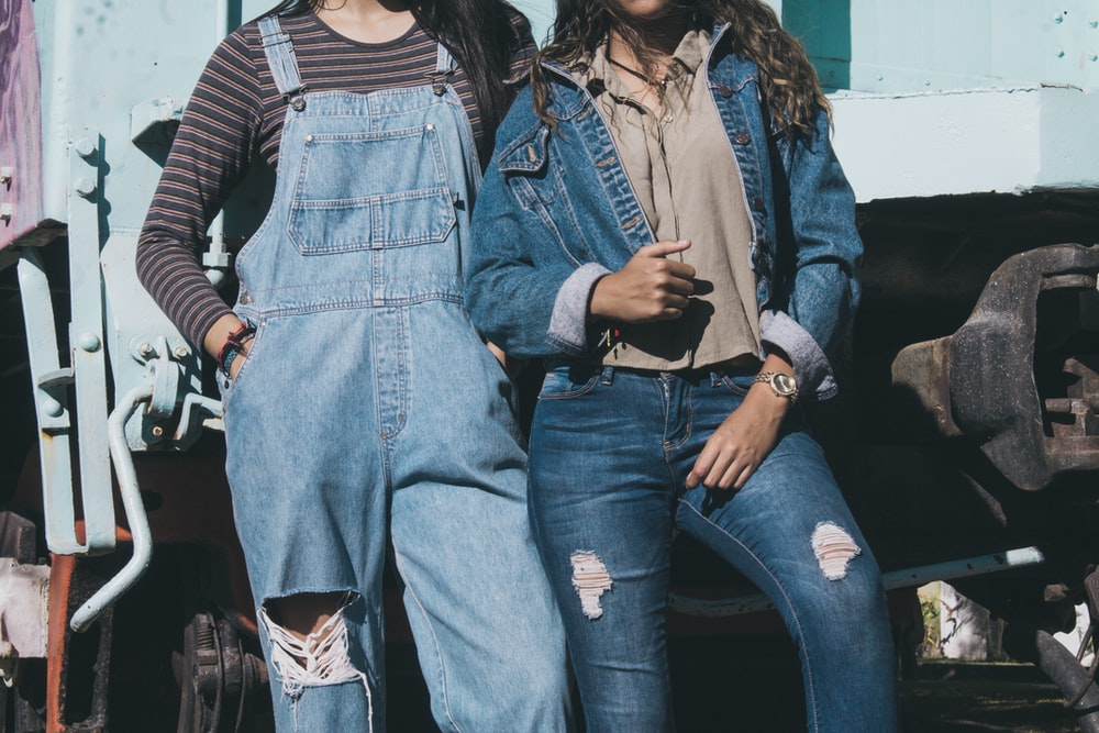 two women standing side by side wearing denim dungarees and jacket
