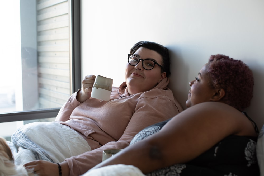 two woman lying on bed