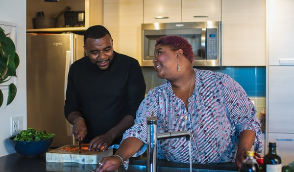 Happy Relationship - Black man and woman couple cooking in the kitchen