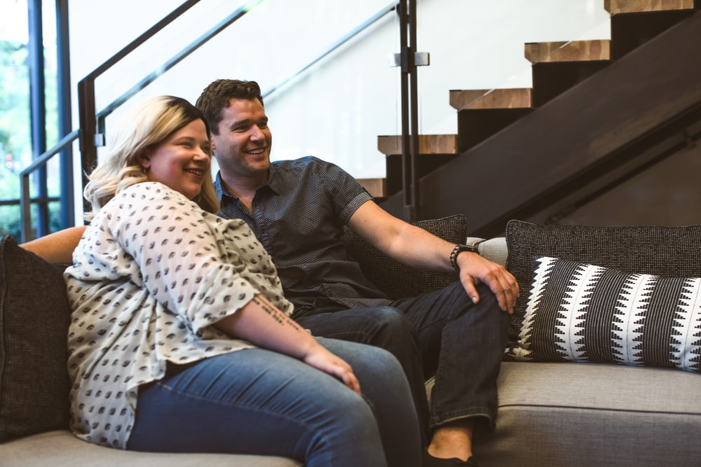 man and woman sitting on sofa smiling