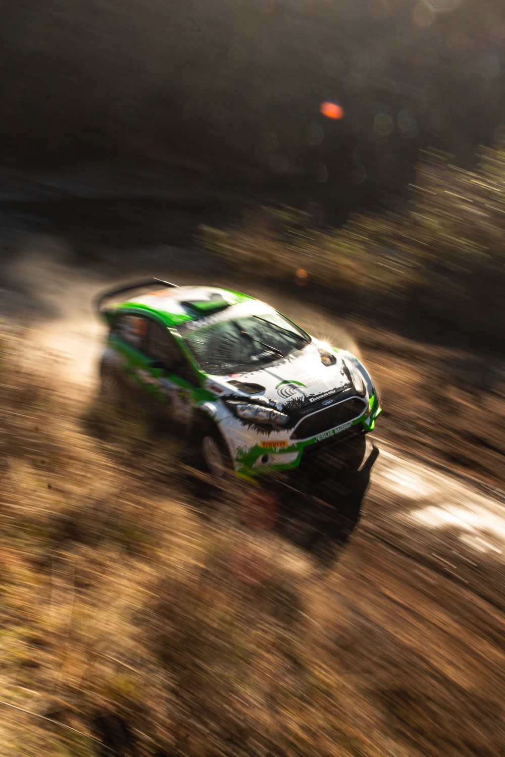 white and green racing car on dirt road
