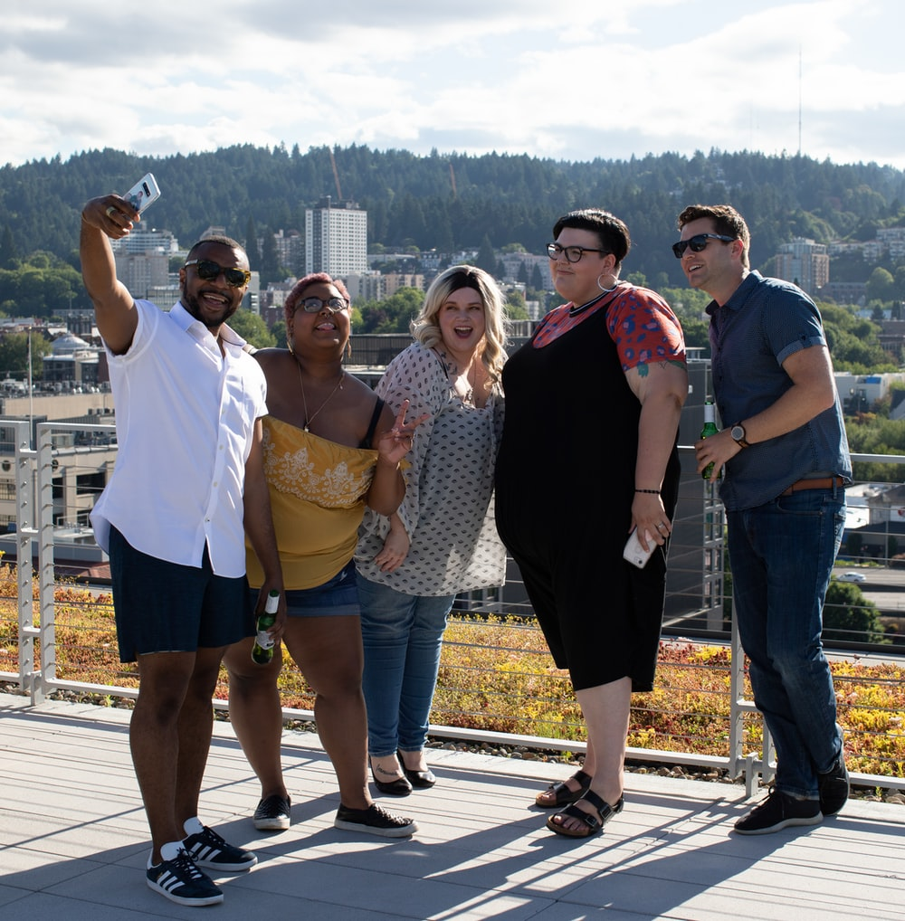 five people standing near railings