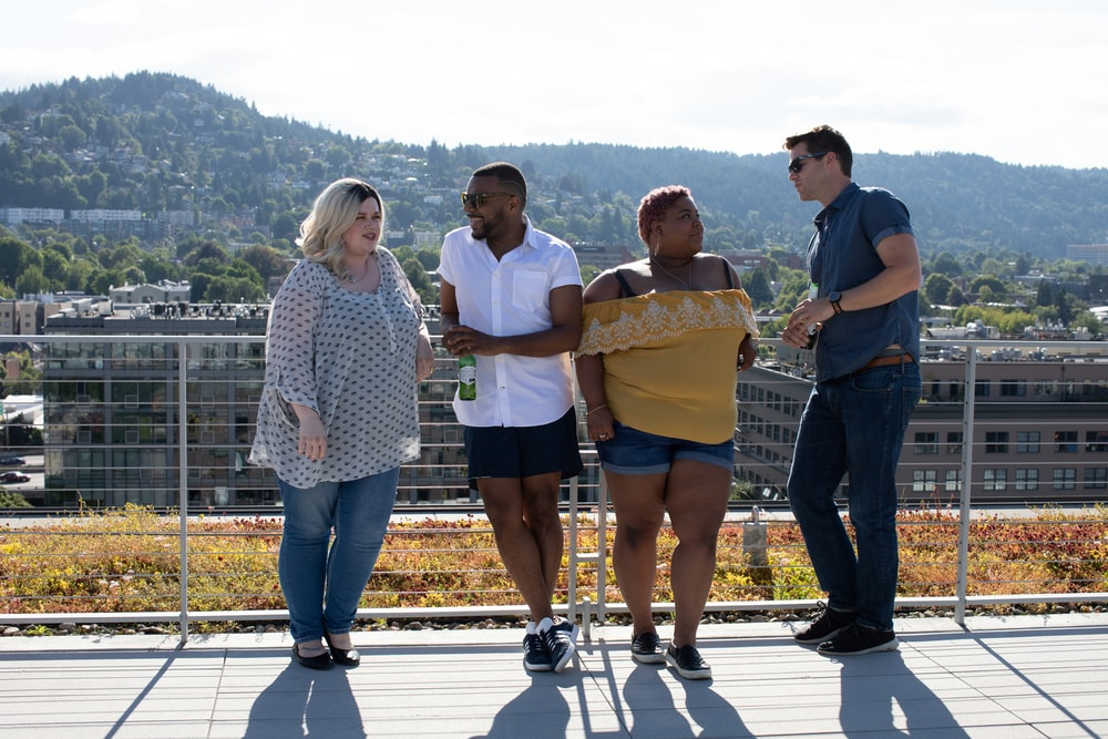 four people leaning on railings