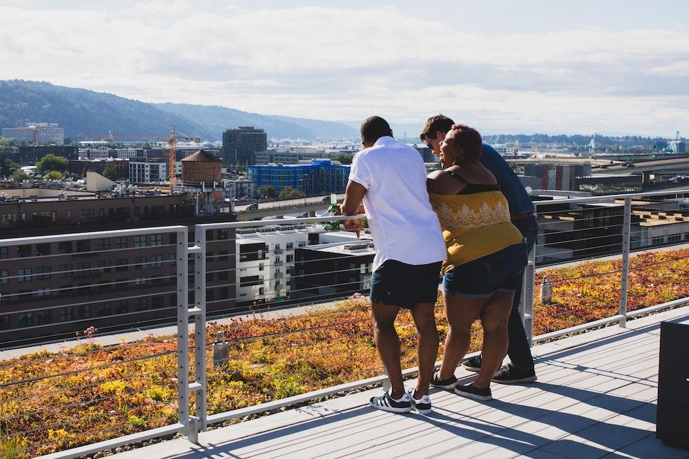 three people leaning on railing
